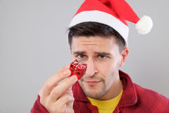 Closeup portrait unhappy, upset man holding small red gift Stock Photos