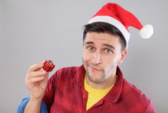 Closeup portrait unhappy, upset man holding small red gift Stock Photography