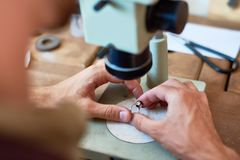 Pawn Shop Appraiser. Closeup portrait of unrecognizable jeweler inspecting ring using microscope on workshop table royalty free stock photo