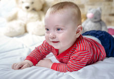 Closeup portrait view of one funny smiling cute little baby boy with blonde hair lying on bed with soft blanket looking forward Royalty Free Stock Photo
