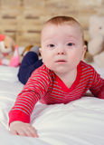 Closeup portrait view of one funny smiling cute little baby boy with blonde hair lying on bed with soft blanket looking forward Royalty Free Stock Photos