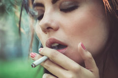Closeup portrait of white Caucasian beautiful young sexy brunette woman with closed eyes smoking cigarette Royalty Free Stock Images