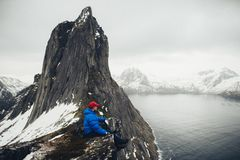 Closeup portrait of winter adventurer over sky and snow backgrou. Life on the edge Traveler on cliff mountains over fjord enjoying Norway landscape Travel Stock Photos