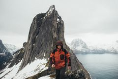 Closeup portrait of winter adventurer over sky and snow backgrou. Traveler with backpack and mountain panorama. Norway Royalty Free Stock Photo