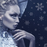 Closeup portrait of winter queen. Closeup portrait of beautiful young woman dressed as winter queen. Creative makeup. Over black background. Copy space Royalty Free Stock Photo