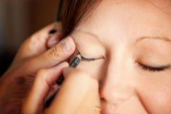 Makeup artist paints eyes royalty free stock image