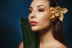 Closeup portrait of woman with slicked back hair, tender lily flower behind ear. Looking away. Beauty concept. Royalty Free Stock Photos