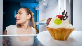 Closeup portrait of young woman sneaking in refrigerator for something to eat. Closeup portrait of woman sneaking in refrigerator for something to eat Royalty Free Stock Photos
