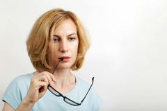 Closeup portrait of a woman takes off her glasses royalty free stock photos