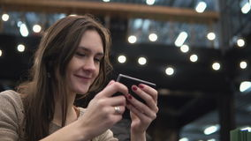 Closeup portrait. Woman using her smartphon touchscreen device in modern cafe lights in the background 4k stock video
