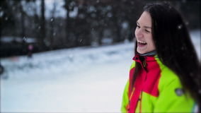Closeup Portrait of Woman Wearing Colorful Ski Suit, Snowflakes Slowly Falling Down. Cute Young Girl with Long Hair and stock video footage