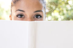 Closeup portrait of woman with white book looking at camera. Royalty Free Stock Images