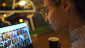 Closeup portrait of woman working at night in cafe and using computer touchscreen, looking at monitor