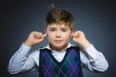 Closeup portrait of worried boy covering his ears, observing. Hear nothing Royalty Free Stock Image