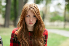 Closeup portrait of young adorable redhead woman in red plaid jacket stares into camera with blurred park background Royalty Free Stock Photography