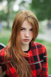 Closeup portrait of young adorable redhead woman in red plaid jacket stares into camera with blurred park background Stock Images
