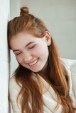 Closeup portrait of young adorable redhead woman wrapped in a white knitted blanket posing near white wall indoor natural light Royalty Free Stock Photography