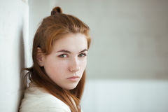 Closeup portrait of young adorable redhead woman wrapped in a white knitted blanket posing near white wall indoor natural light Stock Photo