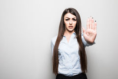 Closeup portrait young annoyed angry woman with bad attitude giving talk to hand gesture with palm outward isolated grey wall back Royalty Free Stock Photo