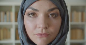 Closeup portrait of young arabian attractive businesswoman in hijab looking at camera in the library indoors.  stock footage