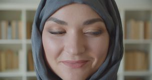 Closeup portrait of young arabian attractive businesswoman in hijab looking at camera smiling cheerfully in the library. Indoors stock video