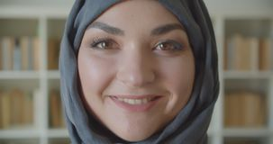 Closeup portrait of young arabian attractive businesswoman in hijab looking at camera smiling cheerfully in the library. Indoors stock footage