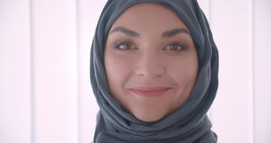 Closeup portrait of young arabian attractive businesswoman in hijab looking at camera smiling happily in the white. Office indoors stock video
