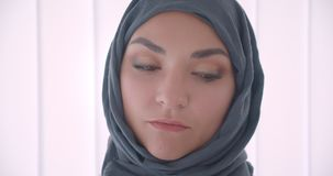 Closeup portrait of young arabian attractive businesswoman in hijab looking at camera in the white apartment indoors.  stock video footage