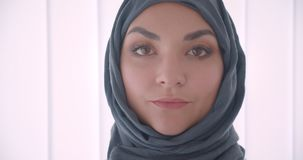 Closeup portrait of young arabian attractive businesswoman in hijab looking at camera in the white office indoors.  stock video footage