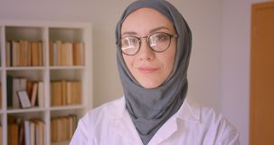 Closeup portrait of young arabian female doctor in glasses and hijab looking at camera smiling cheerfully in library. Indoors stock footage