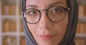 Closeup portrait of young arabian female face in glasses and hijab looking at camera smiling cheerfully in library. Indoors stock footage