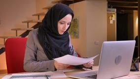 Closeup portrait of young arabian female office worker analyzing the data on the graph using the laptop and making notes. On the workplace indoors stock video footage