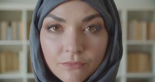 Closeup portrait of young arabian pretty businesswoman in hijab looking at camera in the library indoors.  stock video