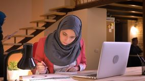 Closeup portrait of young attentive muslim businesswoman in hijab studying the data on the graph in front of the laptop. Indoors on the workplace stock video footage
