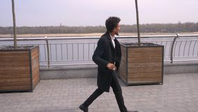 Closeup portrait of young attractive african american businessman walking and dancing happily on the street in the urban. City stock footage