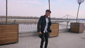 Closeup portrait of young attractive african american businessman walking dancing looking at camera and smiling. Cheerfully on the street in the urban city stock video footage