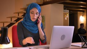 Closeup portrait of young attractive arabian female employee having a formal conversation on the phone while typing on. The laptop stock footage