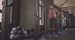 Closeup portrait of young attractive athletic muslim female in hijab doing leg resistance training in gym indoors.  stock video footage