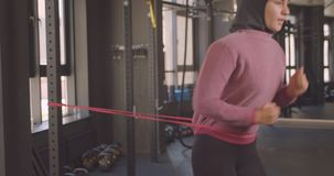 Closeup portrait of young attractive athletic muslim female in hijab jogging doing resistance training in gym indoors.  stock footage