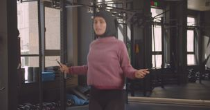 Closeup portrait of young attractive athletic muslim female in hijab jumping rope in gym indoors.  stock video footage