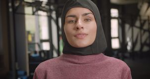 Closeup portrait of young attractive athletic muslim female looking at camera being motivated standing in gym indoors.  stock video