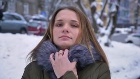 Closeup portrait of young attractive caucasian female with brunette hair freezing and hiding in a cozy winter coat in a. Snowy day stock footage