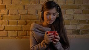 Closeup portrait of young attractive caucasian female listening to music in headphones while sitting on the couch and. Holding a cup of warm tea stock photo