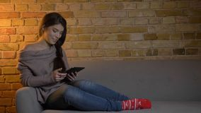 Closeup portrait of young attractive caucasian female using the tablet while resting laidback on the couch and smiling royalty free stock images