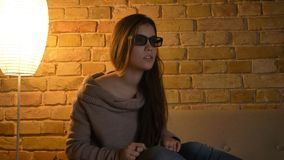 Closeup portrait of young attractive caucasian female watching a movie on TV in 3D glasses with excited facial stock photography