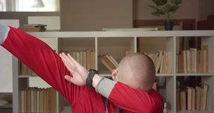 Closeup portrait of young attractive caucasian male student dabbing with confidence looking at camera in the college. Library indoors stock footage