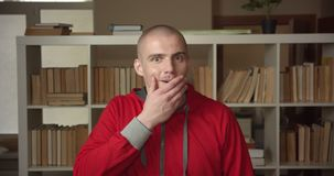 Closeup portrait of young attractive caucasian male student getting excited and surprised looking at camera in the. College library indoors stock video
