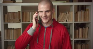 Closeup portrait of young attractive caucasian male student having a phone call in the college library indoors.  stock video