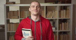 Closeup portrait of young attractive caucasian male student holding a book looking at camera and smiling in the college. Library indoors stock video footage