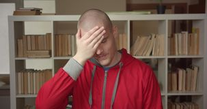 Closeup portrait of young attractive caucasian male student making a face palm being annoyed looking at camera in the. College library indoors stock video